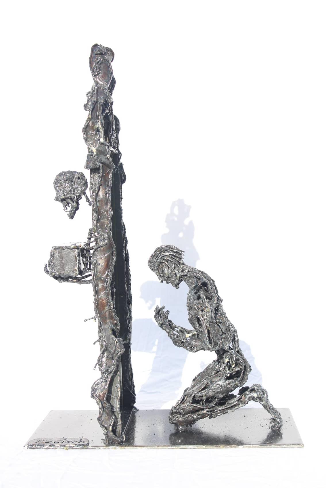 Sculpture d'un personnage à genoux en métal